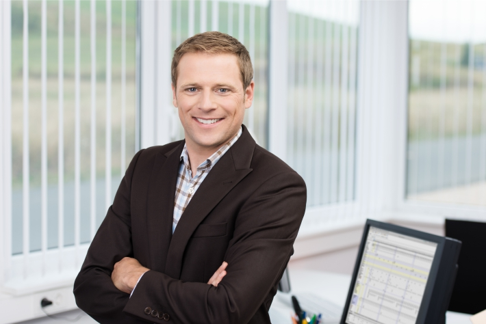Smiling business man stood in front of a desk